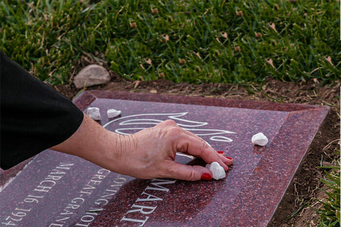 Many people mark their visits to the cemetery by leaving stones by the grave.
